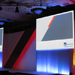 AXA Wealth branded podium with two large projector screens, custom backdrop and central podium