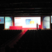 Conference theatre with five projector screens and individual presenting on stage